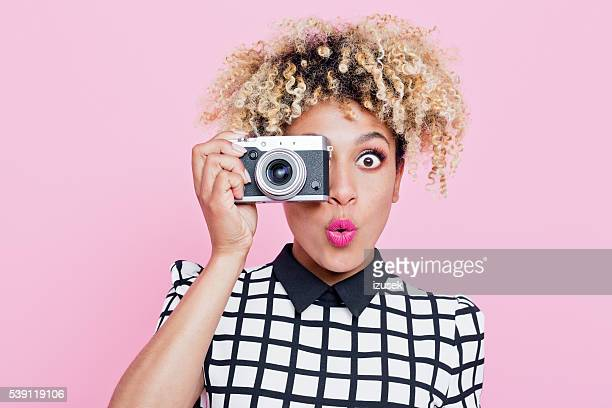 surprised young woman wearing sunglasses, holding camera - photographer stock photos and pictures
