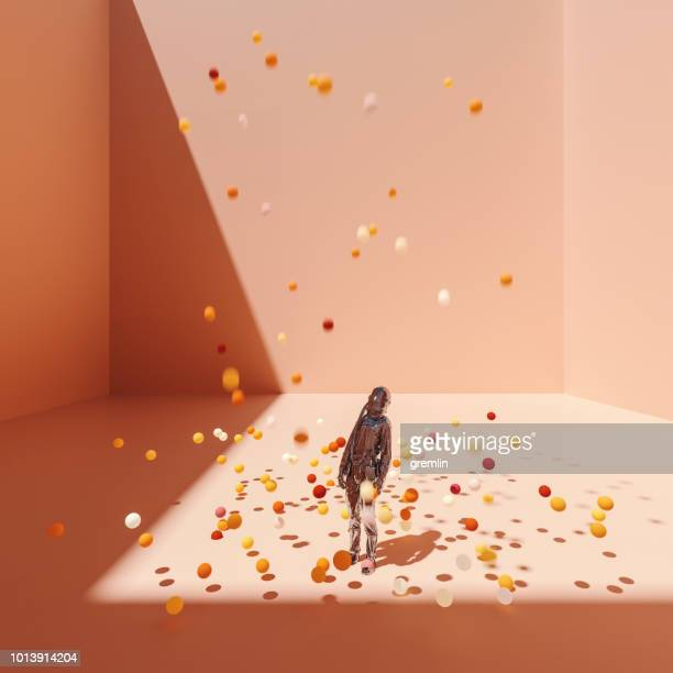 surreal bent astronaut in cubic room with falling spheres - bouncing stock pictures, royalty-free photos & images