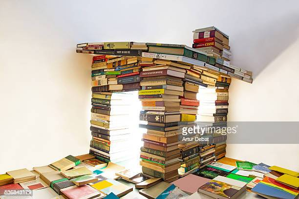 Surreal house made of books with white background.