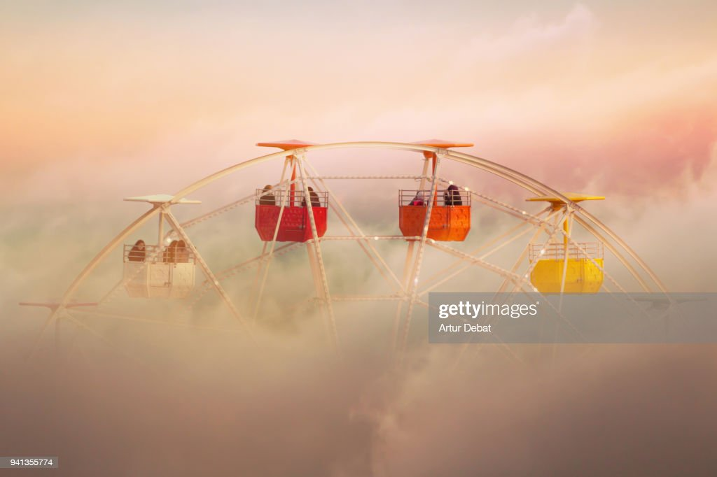Surreal picture of colorful ferris wheel emerging from the clouds. : Foto de stock