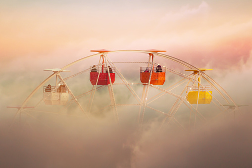 Surreal picture of colorful ferris wheel emerging from the clouds. - gettyimageskorea