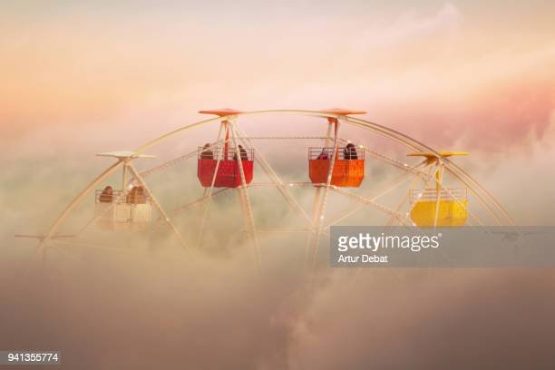 Surreal picture of colorful ferris wheel emerging from the clouds.