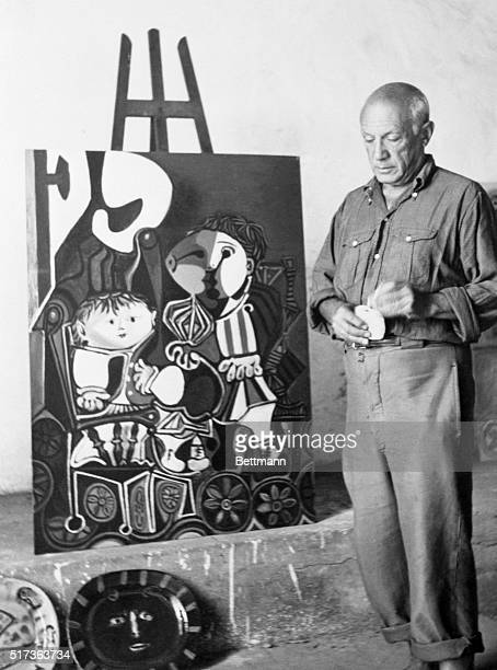 Surrealistic high priest Pablo Picasso modestly averts his eyes as the camera catches him with a few of his new creations showing At his southers...