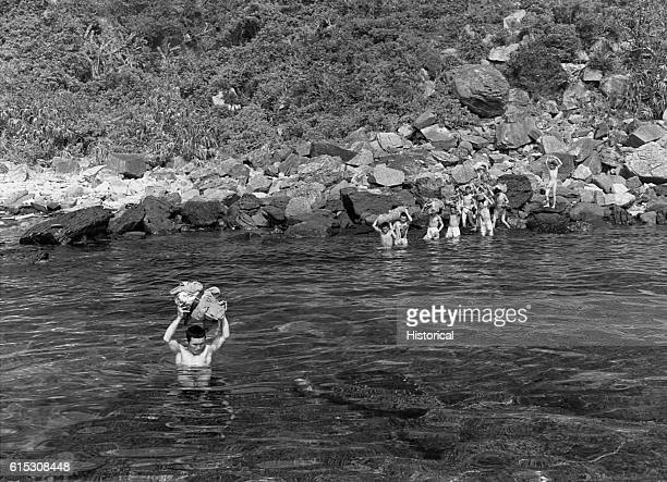 Surrendering Japanese soldiers wade through the water towards a Navy picket boat on Kerama-retto during the Okinawa campaign. May 1945.