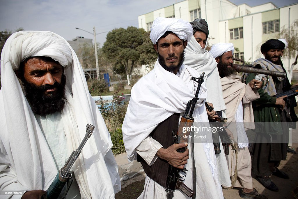 Surrendering Taliban militants stand with their weapons as they are presented to the media on November 4, 2010 in Herat, Afghanistan. Twenty Taliban fighters from Afghanistan's Herat province have surrendered to government troops in Herat, west of the capital city of Kabul. After an amnesty launched by President Hamid Karzai in November 2004, hundreds of anti-government Taliban militants have since surrendered to the government.