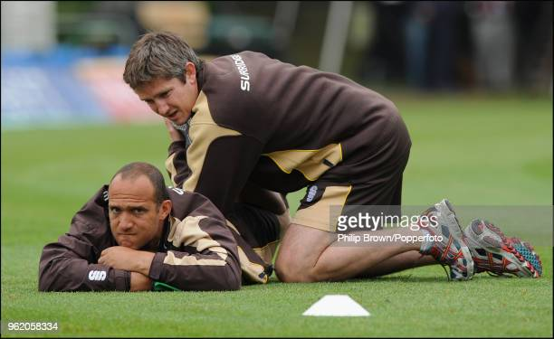 Surrey captain Mark Butcher gets help stretching before the LV County Championship match between Surrey and Somerset at Whitgift School, Croydon,...