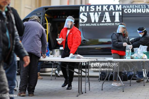 Surrey Cricketer Amar Virdi helping to distribute food to the homeless and those in need with NishkamSWAT in Trafalgar Square on May 13, 2020 in...