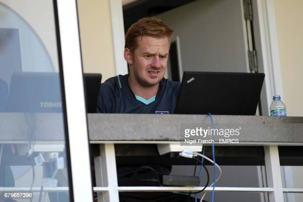 Surrey Professional squad analyst & performance manager David Court on his laptop whilst sitting on the balcony for the start of play