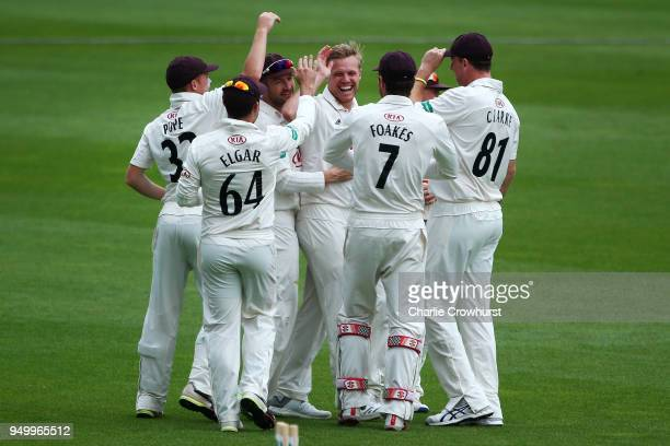 Surrey's Matt Dunn celebrates with team mates after taking the wicket of Hampshire's Lewis McManus during day three of the Specsavers County...