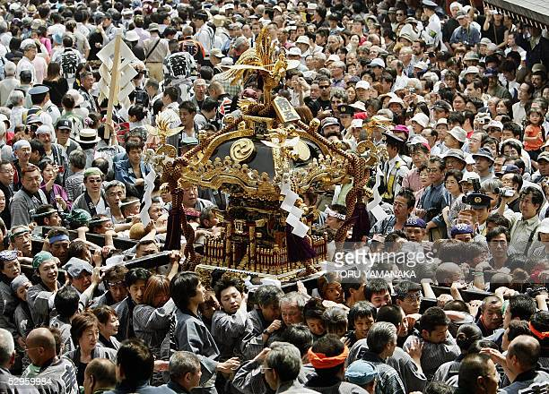 Surrounded by a crowd Japanese youth wearing traditional costumes carry a portable shrine on the approach to the Sensoji Temple during Tokyo's...