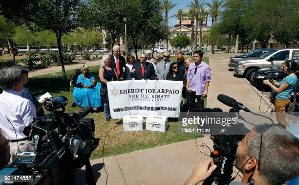 Surrounded by a group of supporters former Maricopa County Sheriff Joe Arpaio speaks to the media in front of the Arizona State Capitol before filing...