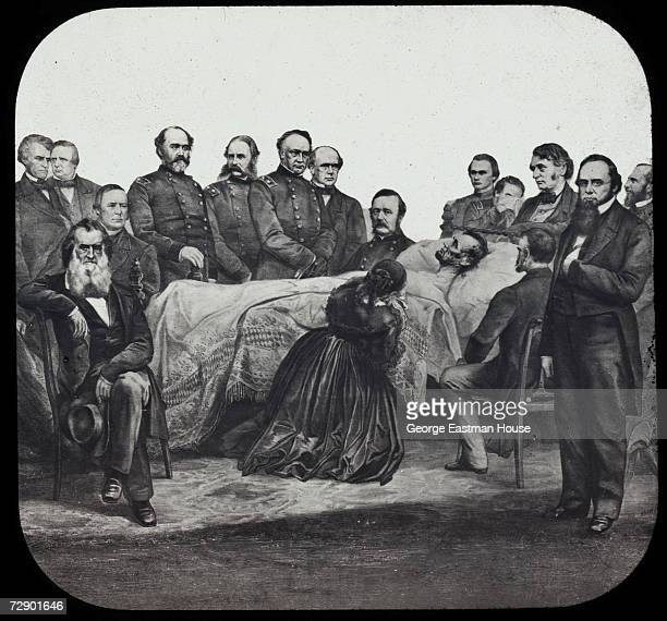 Surrounded by a large group of men American First Lady Mary Todd Lincoln kneels at the bedside of her husband American President Abraham Lincoln who...