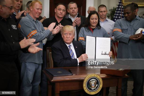 Surrounded by applauding steel and aluminum workers US President Donald Trump holds up the 'Section 232 Proclamations' on steel imports that he...