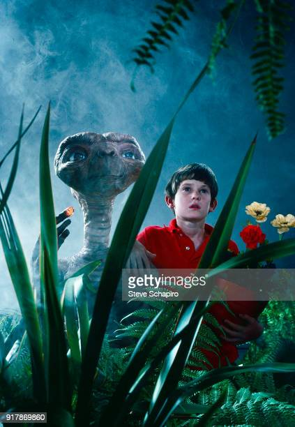 Surrounded by artificial vegetation American child actor Henry Thomas poses with the titular puppet from his film 'ET the Extra Terrestrial' Los...