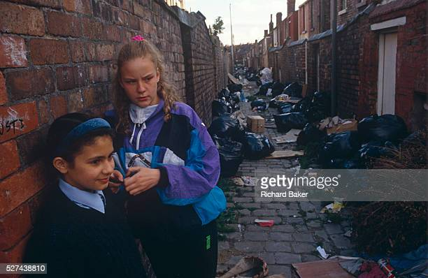 Surrounded by black binbags during the Merseyside dustmans' strike of 1991 two young 'Scouse' girls lean against a brick wall in a rear alleyway...
