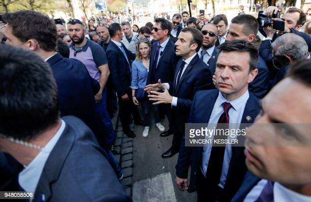 Surrounded by body guards, French President Emmanuel Macron argues with demonstrators opposed to his reforms on April 18, 2018 as he was visiting the...