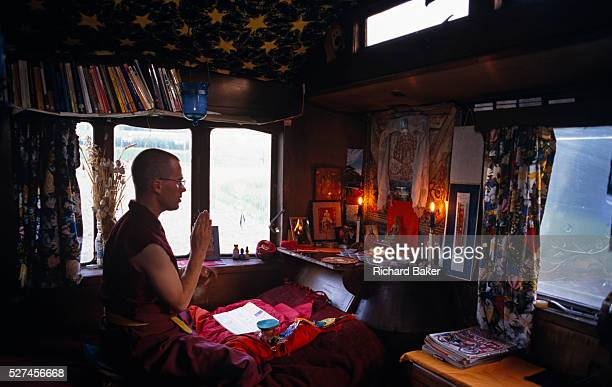 Surrounded by books and holy relics a monk follower of TibetanBuddhism engages in Puja or prayer at the Kagyu Samye Ling Monastery and Tibetan Centre...