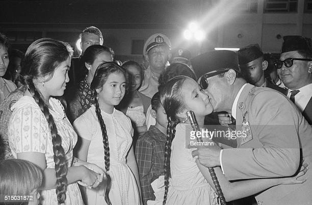 Surrounded by citizens of Jakarta President Sukarno kisses his youngest daughter Sukmawati goodbye while his other daughters Rachmawati and Megawati...