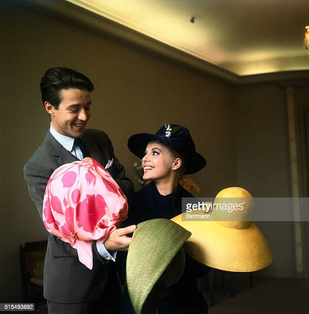 Surrounded by colorful wide-brimmed hats, Italian star Virna Lisi finds it hard to choose the one she really wants. Lending her a hand is Bergdorf...