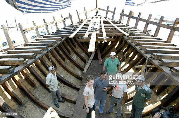 Surrounded by craftsmen Syrian First Lady Asma alAssad listens on as she stands in the hull of a replica of a Phoenician ship being built on the...