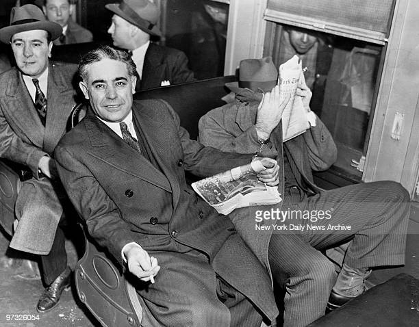 Surrounded by deputy sheriffs and shackled together Emanuel Weiss covering his face and Louis Capone sit on the train en route to Sing Sing prison