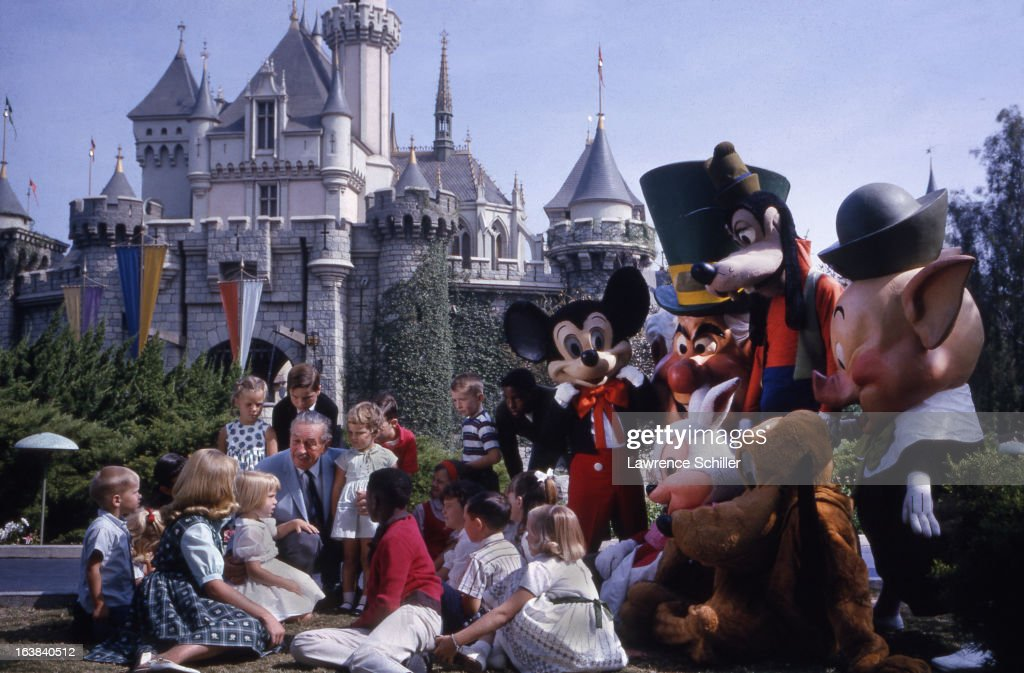 Surrounded by Disney character actors, American businessman, animator, and director Walt Disney (1901 - 1966) (center) speaks with a group of children at the Disneyland theme park, Anaheim, California, 1964.