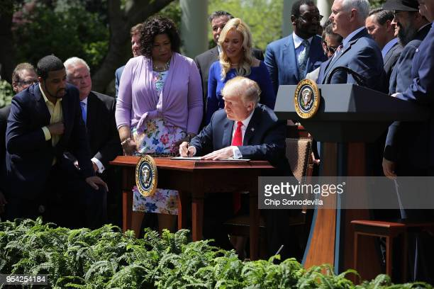 Surrounded by faith leaders US President Donald Trump signs an executive order to establish a White House Faith and Opportunity Initiative during an...