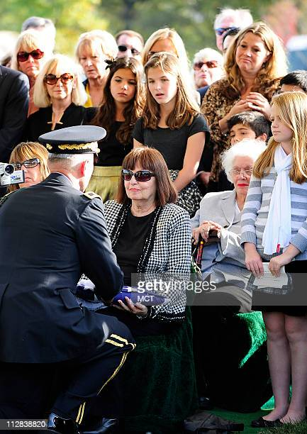 Surrounded by family and friends Marilyn Duell of Miami Florida the oldest niece of the family of Sgt John R Simonetti receives the flag from his...