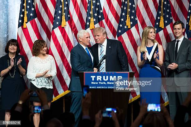 Surrounded by family members Republican presidential candidate Donald Trump stands with his newly selected vice presidential running mate Mike Pence...