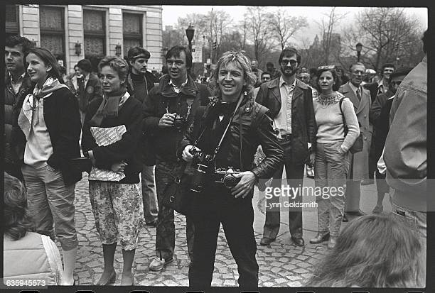 Surrounded by fans guitarist Andy Summers of rock band The Police holds a camera and smiles