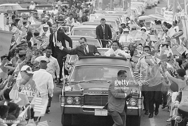 Surrounded by flagwaving crowd Pres Richard Nixon and Philippines Pres Ferdinand E Marcos wave from car during motorcade to Malacanang Palace here...
