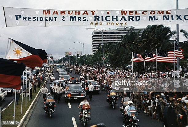 Surrounded by flagwaving crowd President Richard Nixon and Philippines President Ferdinand E Marcos wave from car during motorcade to Malacanang...