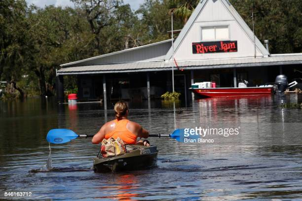 Surrounded by floodwater from nearby the Peace River Summer Lempanau uses a kayak to deliver food to workers at her business the Peace River...