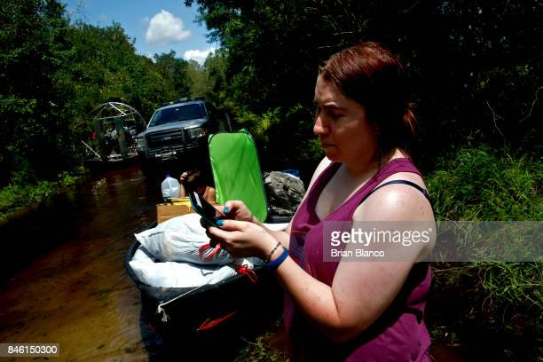 Surrounded by floodwater from the nearby Peace River Robyn Barber checks her phone's battery power percentage as she waits with the boat with her two...
