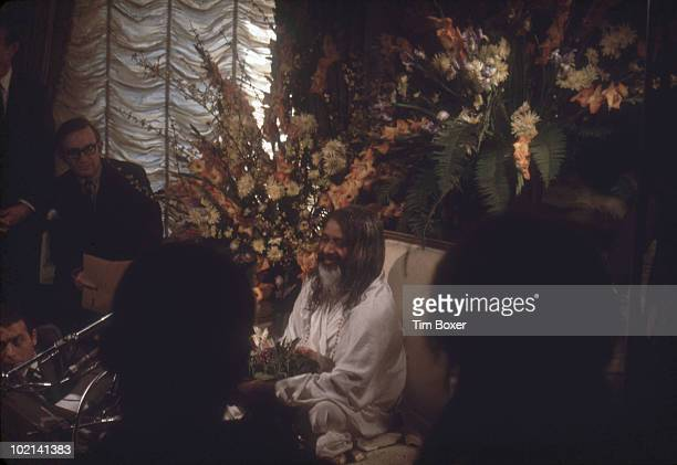 Surrounded by flowers Indian guru of the Transcendental Meditation movement Maharishi Mahesh Yogi sits on a sofa as he gives a press conference...