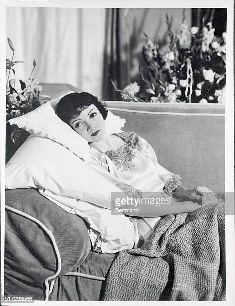 Surrounded by flowers sent by sympathic friends Claudette Colbert recuperates from a recent appendicitis operation at Los Angeles Miss Colbert was...