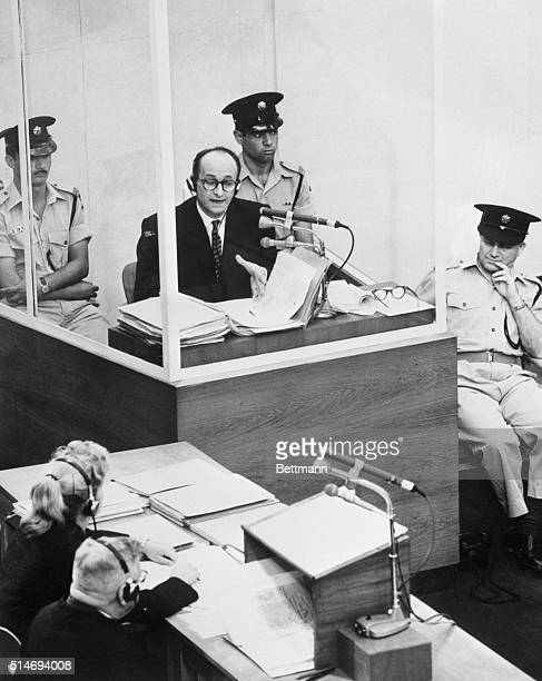 Surrounded by guards and bulletproof glass former SS officer Adolf Eichmann testifies at his trial in Jerusalem