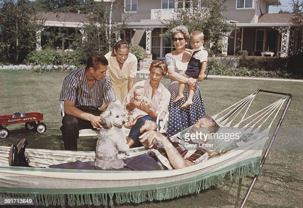 Surrounded by his family American movie producer artist and animator Walt Disney lies in a hammock in the garden with a poodle on his lap 1950s Among...