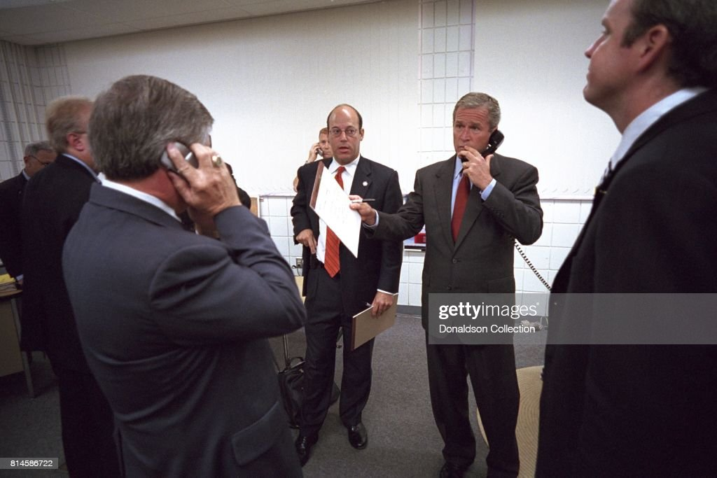 Surrounded by his staff, President George W. Bush calls New York Governor George Pataki, FBI Director Robert Mueller and Vice President Dick Cheney Tuesday, Sept. 11, 2001, from Emma E. Booker Elementary School in Sarasota, Fla. Pictured from left are: Andy Card, White House Chief of Staff; Ari Fleischer, Press Secretary, and Dan Bartlett, Deputy Assistant to the President. Photo by Eric Draper, Courtesy of the George W. Bush Presidential Library/Getty Images