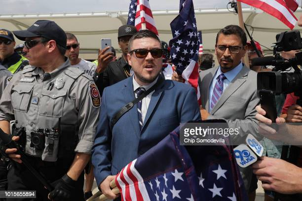 Surrounded by his supporters reporters and Fairfax County Police Jason Kessler walks toward the Vienna/Fairfax GMU Metro Station to travel by train...