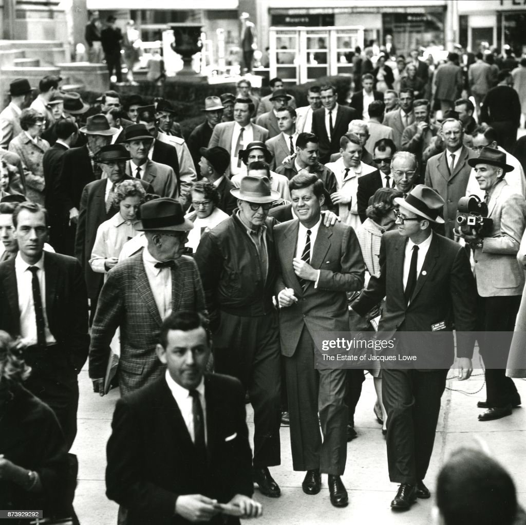 Surrounded by journalists, staffers, and members of the public, Senator (and future US President) John F Kennedy (1917 - 1963) (center right, in striped necktie) smiles as he walks with an unidentified man during a campaign stop, Charleston, West Virginia, April 1960.