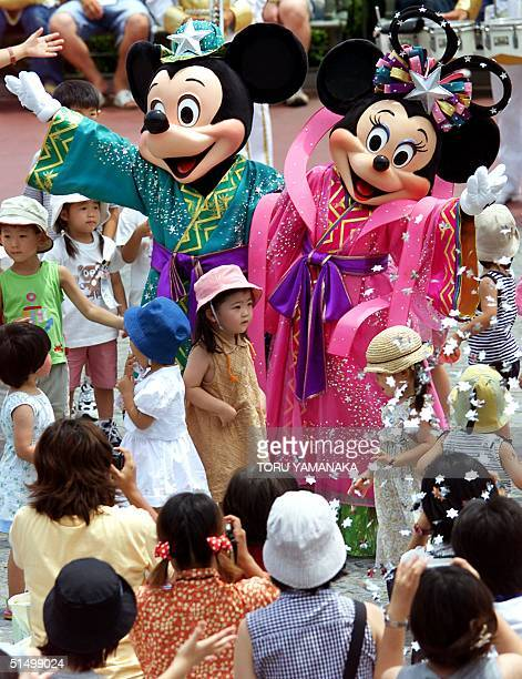 Surrounded by kids and their parents Mickey Mouse and Minnie Mouse who play the parts of Altair the Cowherd and Vega the Weaver perform to celebrate...