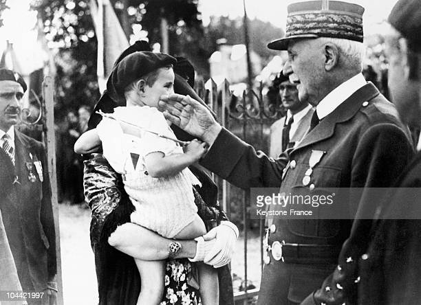 Surrounded By Members Of The French Legion Of Combattants Marshal Petain Strokes The Cheek Of A Young French Citizen Who Came To Honor His Visit...