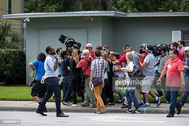 Surrounded by members of the media family and friends of the victims of the Pulse Nightclub shooting walk to their cars as they leave the Beardall...