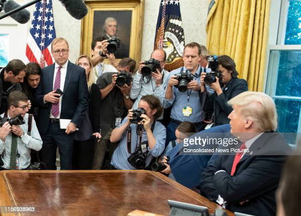Surrounded by members of the press and others, American journalist Jonathan Karl listens to real estate developer & US President Donald Trump in the...