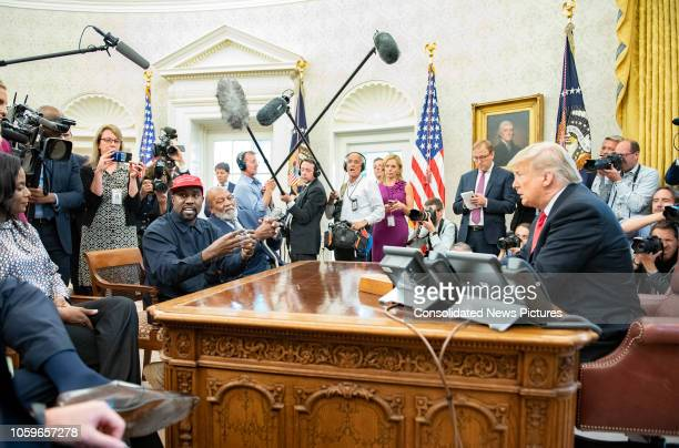 Surrounded by members of the press and others American rapper and producer Kanye West and retired professional football player Jim Brown talk with...