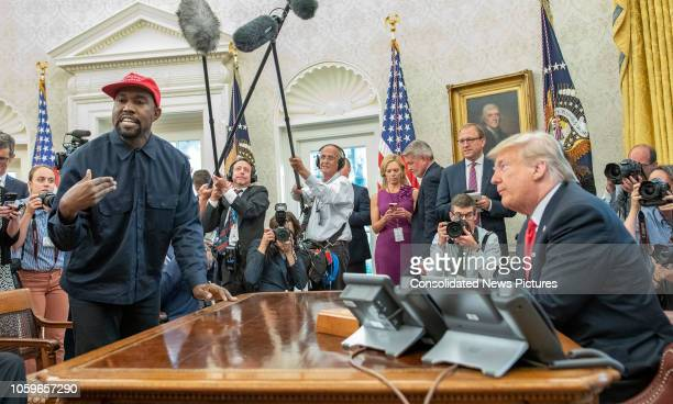 Surrounded by members of the press and others American rapper and producer Kanye West stands as he talks with real estate developer and US President...