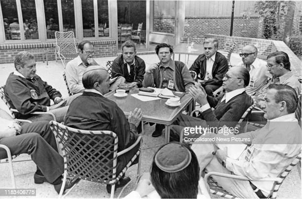 Surrounded by members of their delegation, Israeli Foreign Minister Moshe Dayan and Israeli Prime Minister Menachem Begin talk together during the...