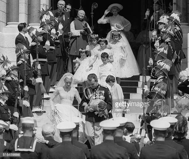 Surrounded by men in uniform Prince Rainier and Princess Grace leave the Cathedral of St. Nicholas, followed by the two page boys and four flower...