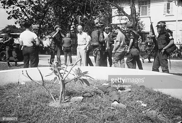 Surrounded by military police journalists and embassy staff US Ambassador Ellsworth Bunker looks at the body of dead Viet Cong soldier on the grounds...
